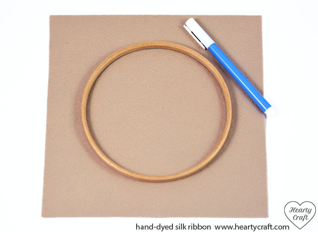 1. Using a water-soluble pen and an inner ring of a small embroidery hoop draw a circle on a piece felt.