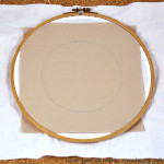 2. Place the felt over a piece of calico and mount both of them in a large hoop. The hoop should be large enough to accommodate the whole ribbon embroidery. My piece of felt is too small for that hoop, but with the large piece of calico I managed to mount it anyway. Even if you've got a sufficiently large piece of felt, use cotton fabric to support it anyway. The felt is easy to deform, and the fabric beneath  it helps to keep the shape.