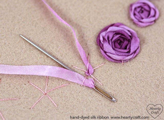 4. Stitch roses using silk ribbon. You can use just one ribbon shade for all roses or make a rainbow as I did.  If you don't have a tapestry needle for weaving, use a chenille one instead, passing it with the the blunt end under and over the spokes.
